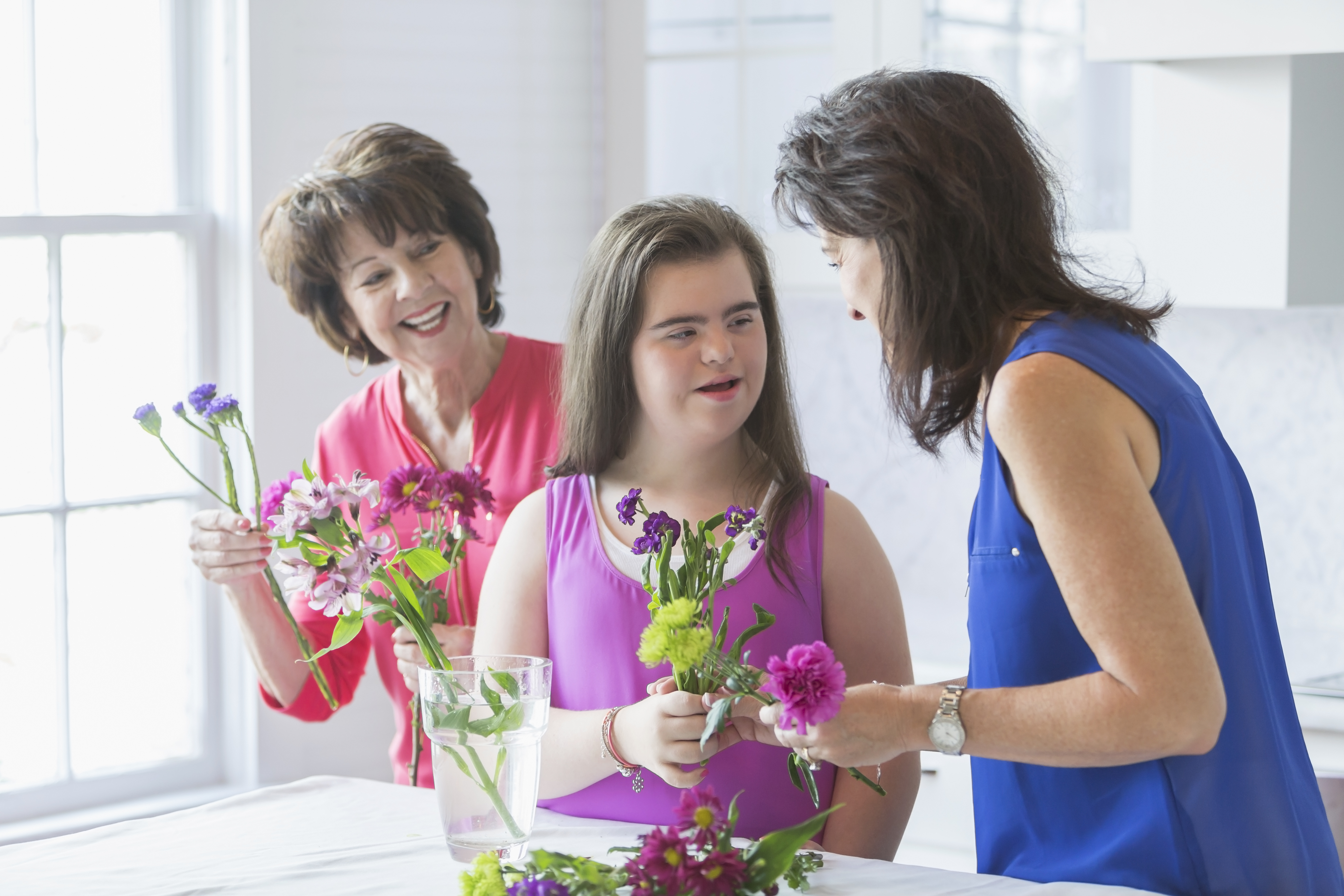 A teenage girl with downs syndrome arranging flowers with her mother and grandmother. They are holding cut flowers in their hands, talking and looking at mom. They are at home in the kitchen by a bright, sunny window.